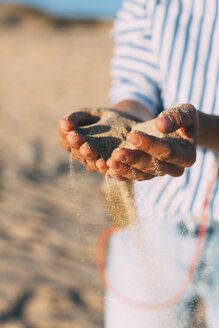 Woman on the beach letting sand trickling through her hands, close-up - JPF00278