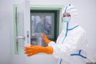 Lab technician wearing cleanroom overall at material sluice - WESTF23658