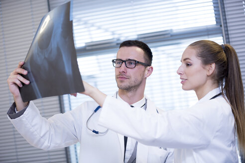 Two doctors discussing x-ray film - WESTF23682