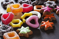 Jelly confectionery, coloured cinnamon stars and other Christmas cookies on dark ground - CSF28545