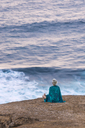 Indonesia, Lombok, woman sitting at the coast looking at view - KNTF00903