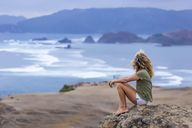 Indonesia, Lombok, woman sitting at the coast looking at view - KNTF00909