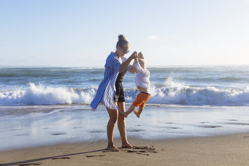 Indonesia, Bali, mother and son playing on the beach - KNTF00912