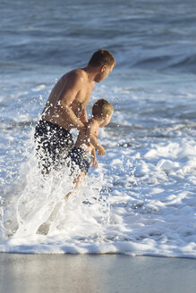 Indonesia, Bali, father and son playing in the ocean - KNTF00915