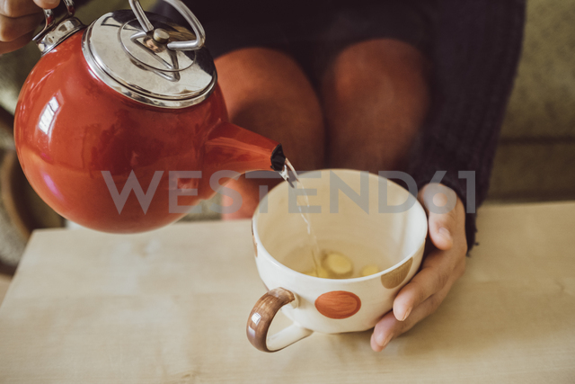 Woman pouring water into tea cup with chopped fresh ginger, close-up - JSCF00013