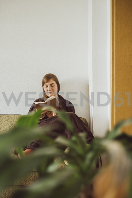 Woman sitting on couch in the living room reading book - JSCF00016