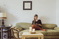 Woman sitting on couch in the living room writing in notebook - JSCF00019