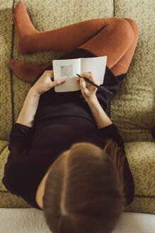 Woman sitting on couch drawing in notebook, top view - JSCF00022