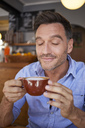 Portrait of smiling man with eyes closed with cup of coffee in a coffee shop - PNEF00341