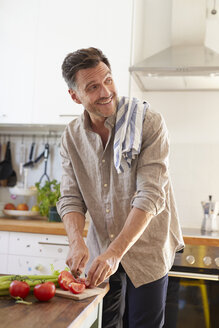 Portrait of laughing man chopping vegetables in the kitchen - PNEF00344
