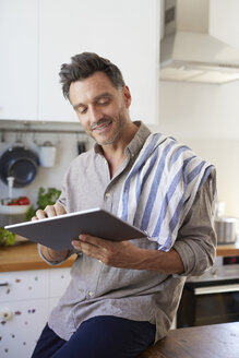 Portrait of smiling man using tablet in the kitchen - PNEF00347