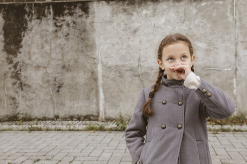 Portrait of little girl with braids wearing grey coat - KMKF00063