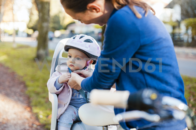 Mother and daughter riding bicycle, baby wearing helmet sitting in children's seat - DIGF03170