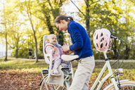 Mother and daughter riding bicycle, baby wearing helmet sitting in children's seat - DIGF03179