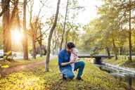 Father searching for chestnuts in park, with baby daughter on his lap - DIGF03185
