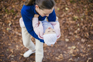 Mother hugging daughter in autumnal park - DIGF03188