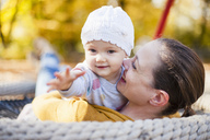 Portrait of baby girl relaxing with her mother on a swing in autumn - DIGF03192