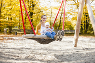 Baby girl sitting with her mother on a swing in autumn - DIGF03195