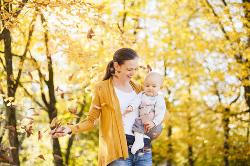 Mother and baby girl having fun with leaves in autumn - DIGF03204