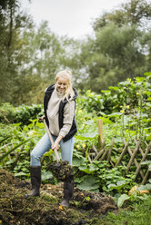 Smiling young woman working with spade in garden - JOSF01880