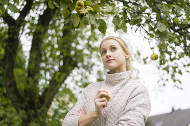 Portrait of young woman at apple tree in garden - JOSF01883
