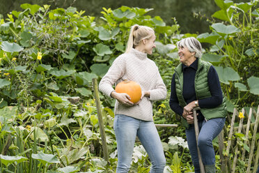 Happy young woman with her grandmother holding pumpkin in garden - JOSF01895