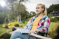 Smiling young woman with book relaxing in garden - JOSF01901