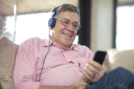 Smiling senior man wearing headphones listening to music at home - ZEF14726