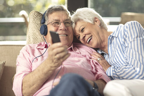 Happy senior couple with cell phone and headphones on couch at home - ZEF14729