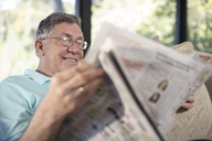 Smiling senior man sitting on couch reading newspaper - ZEF14741