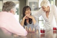 Senior couple playing chess with daughter at home - ZEF14759