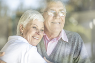 Portrait of smiling senior couple behind windowpane - ZEF14768