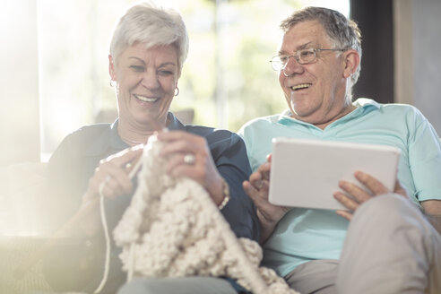 Happy senior couple on couch at home knitting and using tablet - ZEF14774