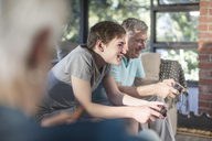 Grandfather and grandson playing video game on couch at home - ZEF14780
