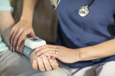 Nurse taking blood pressure of senior patient at home - ZEF14783