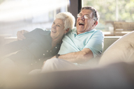 Happy senior couple on couch at home - ZEF14789