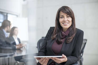 Portrait of smiling businesswoman with tablet on a meeting in conference room - ZEF14810