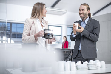 Businessman and businesswoman having coffee in office - ZEF14813