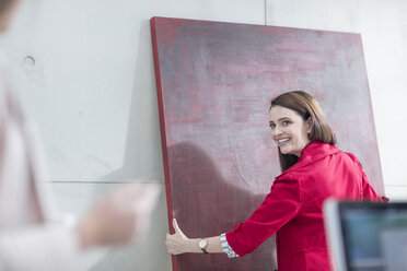 Businesswoman in office holding a red painting - ZEF14816
