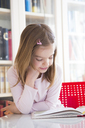 Portrait of smiling little girl at table reading a book - LVF06419
