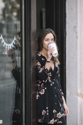 Fashionable woman leaning at entrance door of her shop drinking  coffee to go - ALBF00230