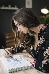 Portrait of woman drawing in sketch book at desk in tattoo studio - ALBF00239