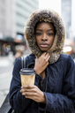 Portrait of fashionable young woman with coffee to go wearing hooded jacket - MAUF01220