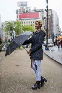 USA, New York City, portrait of laughing young woman with umbrella - MAUF01223