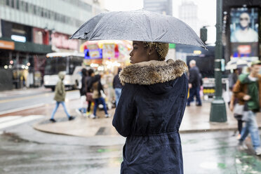 USA, New York City, young woman with umbrella on rainy day - MAUF01226