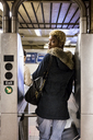 USA, New York City, young woman passing through barrier in subway station - MAUF01235