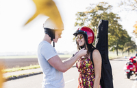 Young man closing helmet of girlfriend with motor scooter in background - UUF12256
