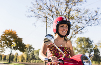 Portrait of smiling young woman on motor scooter - UUF12274