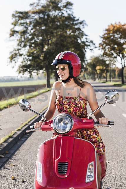 Happy young woman riding motor scooter on country road - UUF12277
