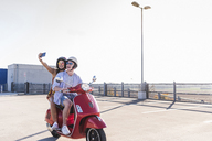 Happy young couple taking a selfie on motor scooter on parking level - UUF12283